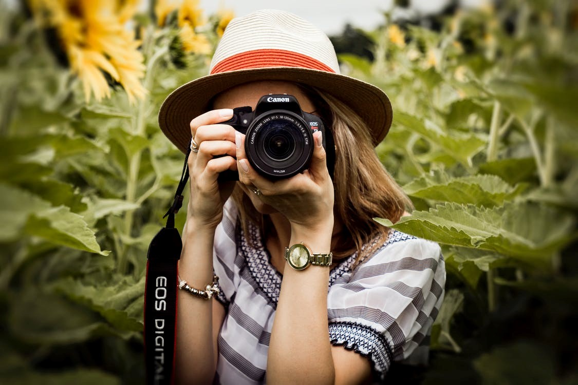 A female photographer holding the camera up to take a picture.